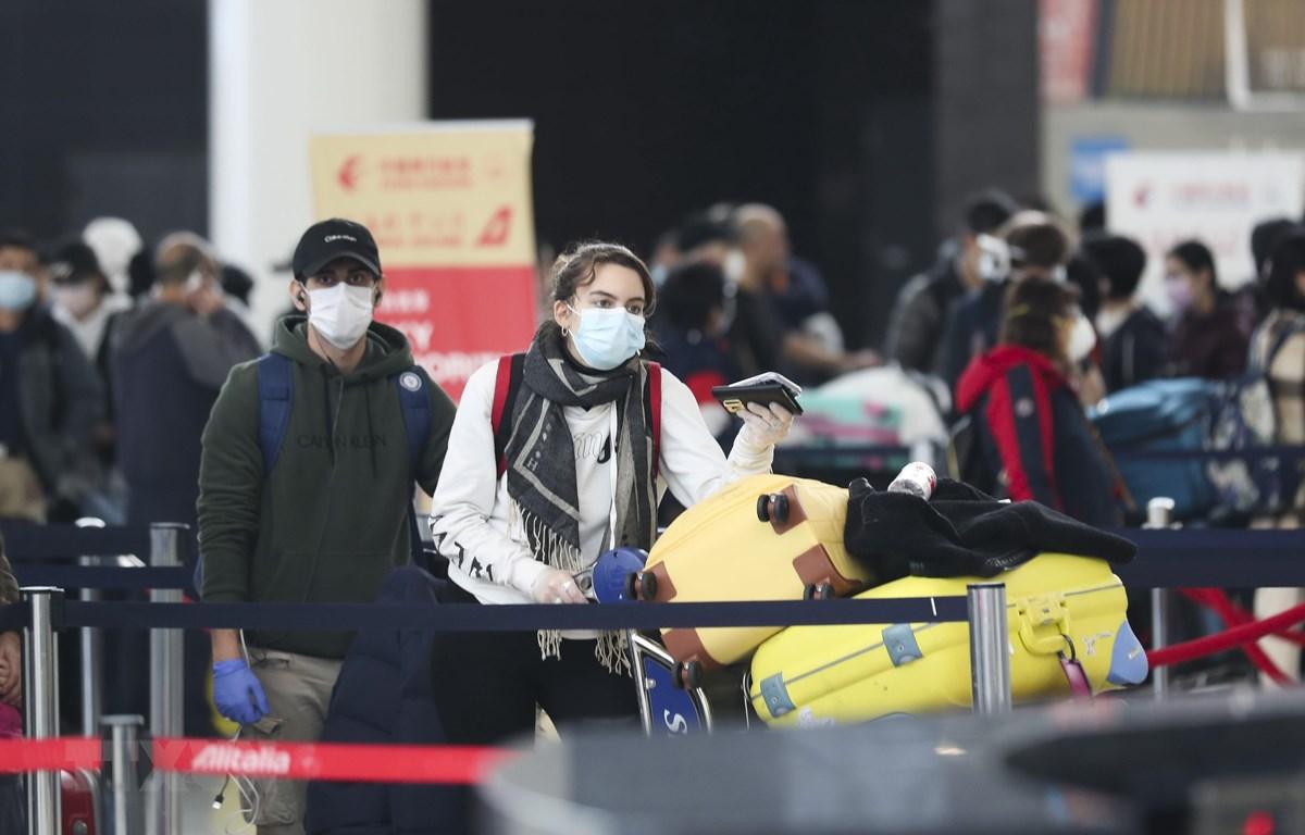 Hành khách đeo khẩu trang phòng dịch COVID-19 tại sân bay quốc tế F.Kennedy ở New York, Mỹ. (Ảnh: THX/TTXVN)