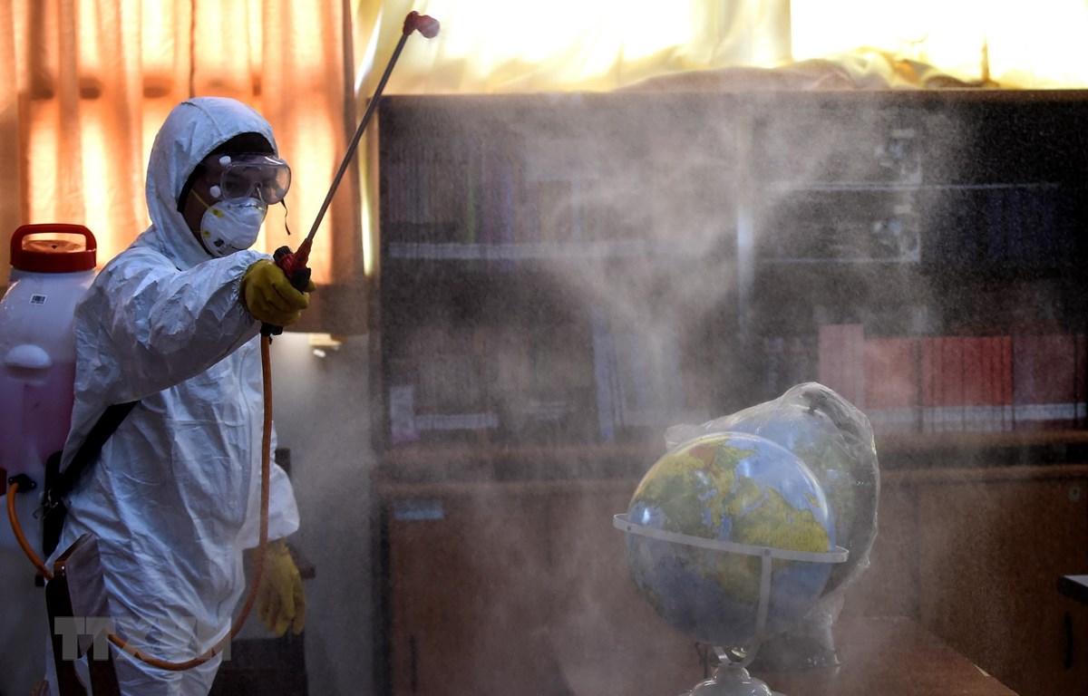 Nhân viên hội Chữ thập đỏ phun thuốc khử trùng tại trường học ở Jakarta, Indonesia, nhằm ngăn chặn sự lây lan của COVID-19. (Ảnh: THX/TTXVN)
