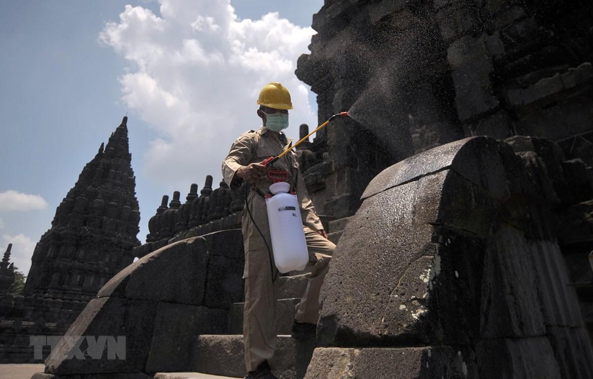 Nhân viên phun thuốc khử trùng tại một ngôi đền ở Trung Java, Indonesia. (Ảnh: THX/TTXVN)