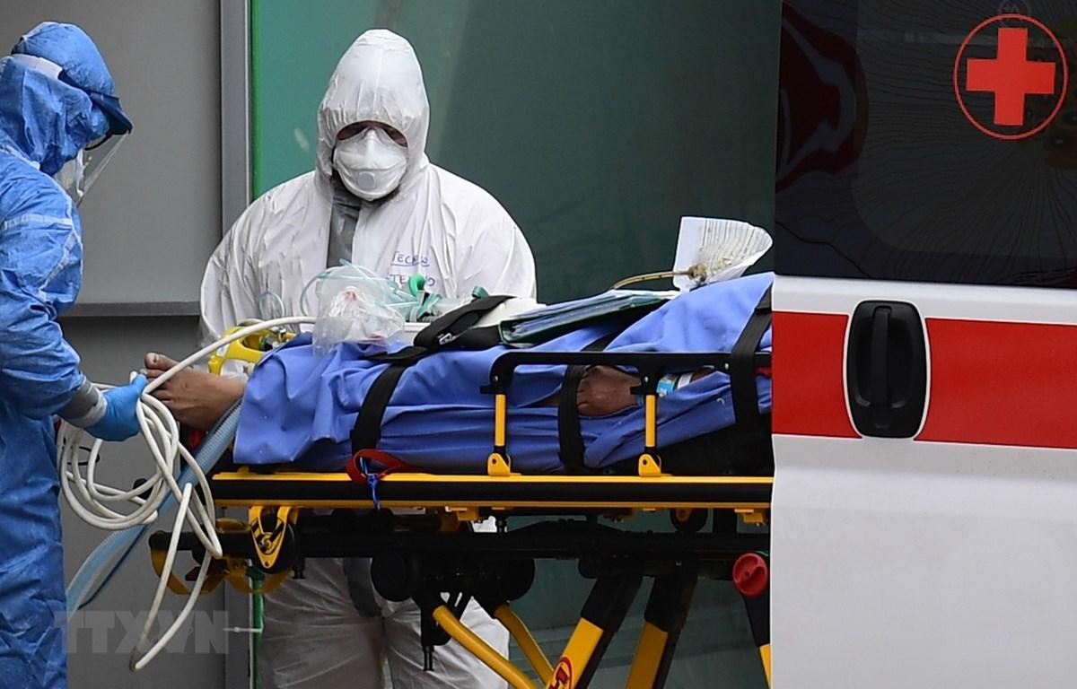 Nhân viên y tế chuyển bệnh nhân nhiễm COVID-19 từ xe cứu thương vào một bệnh viện dã chiến ở Lombardy, Italy. (Ảnh: AFP/TTXVN)