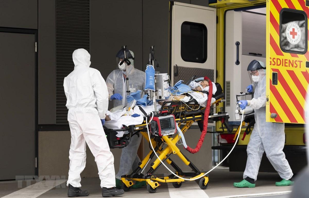 Nhân viên y tế chuyển bệnh nhân mắc COVID-19 từ xe cứu thương vào một bệnh viện ở Dresden, Đức. (Ảnh: AFP/TTXVN)