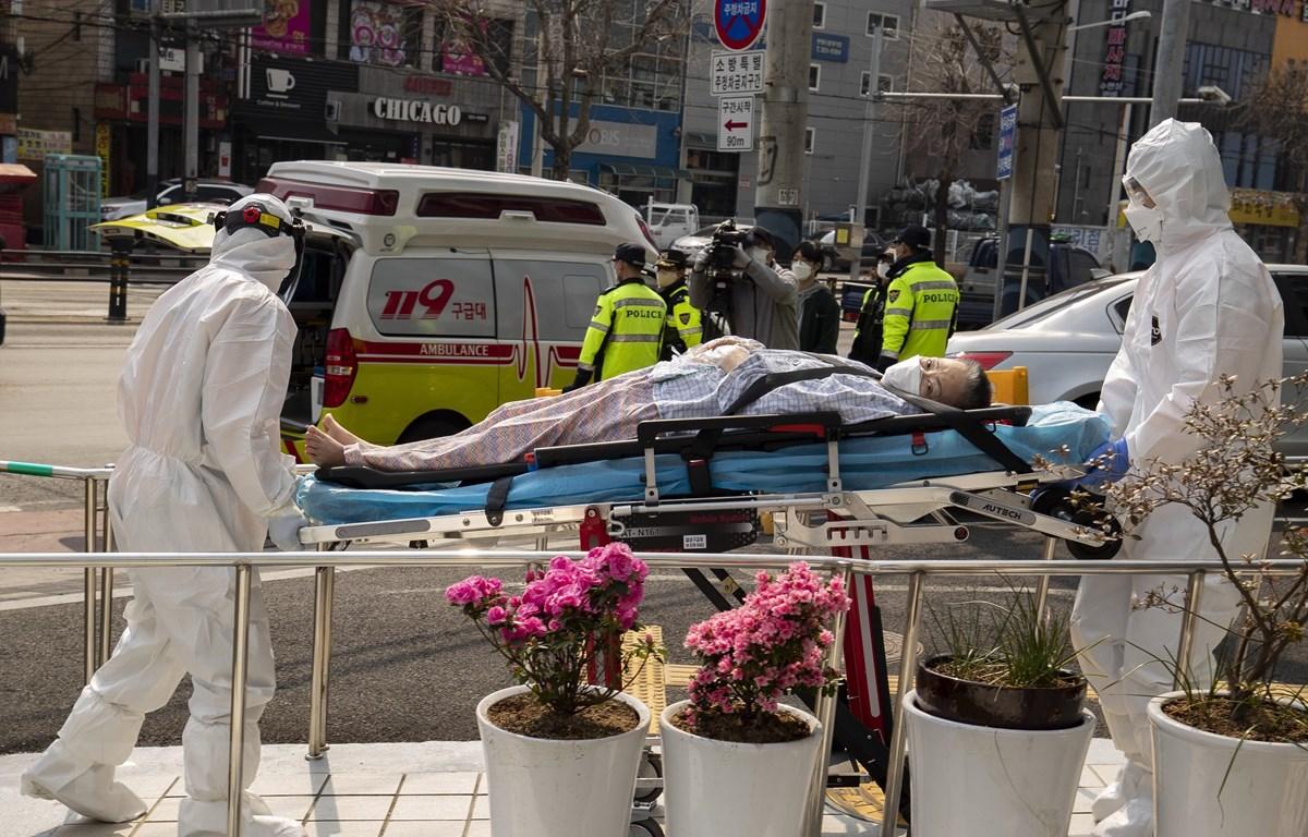 Nhân viên y tế chuyển bệnh nhân nhiễm COVID-19 tới bệnh viện ở Daegu, Hàn Quốc. (Ảnh: THX/TTXVN)