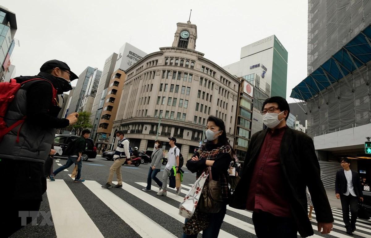 Người dân đeo khẩu trang nhằm ngăn chặn sự lây lan của dịch COVID-19 tại Tokyo, Nhật Bản. (Ảnh: AFP/TTXVN)