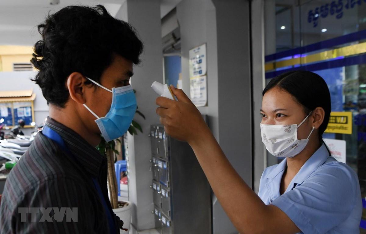 Kiểm tra thân nhiệt người dân trước cửa một ngân hàng nhằm phòng dịch COVID-19 lây lan, tại Phnom Penh, Campuchia. (Ảnh: AFP/TTXVN)