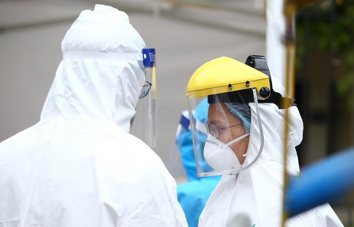 Nhân viên y tế được trang bị đầy đủ quần áo bảo hộ theo đúng quy định phục vụ trạm di động lấy mẫu xét nghiệm. (Ảnh: Minh Quyết/TTXVN)