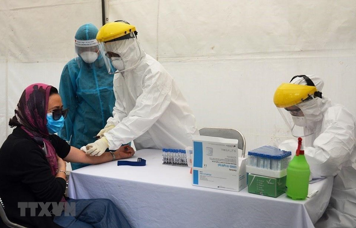 Lấy mẫu xét nghiệm virus SARS-CoV-2 cho người dân tại trạm xét nghiệm nhanh quận Ba Đình. (Ảnh: TTXVN phát)