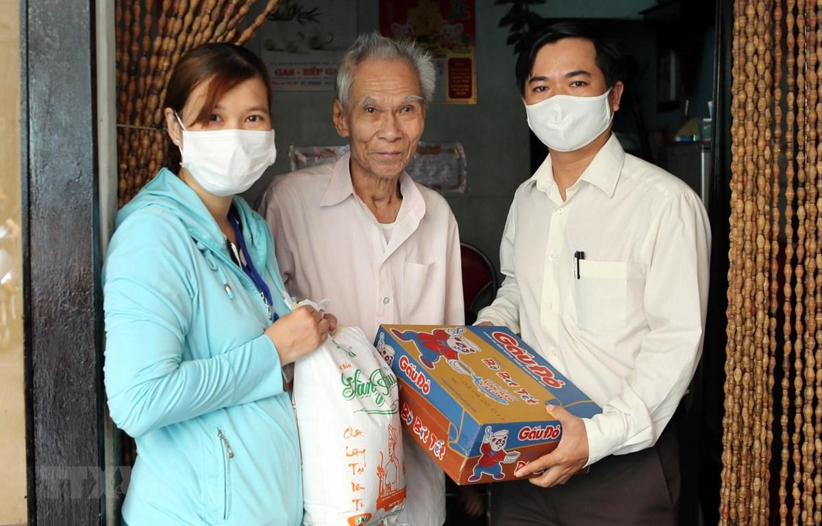 Trao quà hỗ trợ cho gia đình thuộc hộ nghèo có hoàn cảnh khó khăn bị ảnh hưởng do dịch COVID-19. (Ảnh: Trần Lê Lâm/TTXVN)
