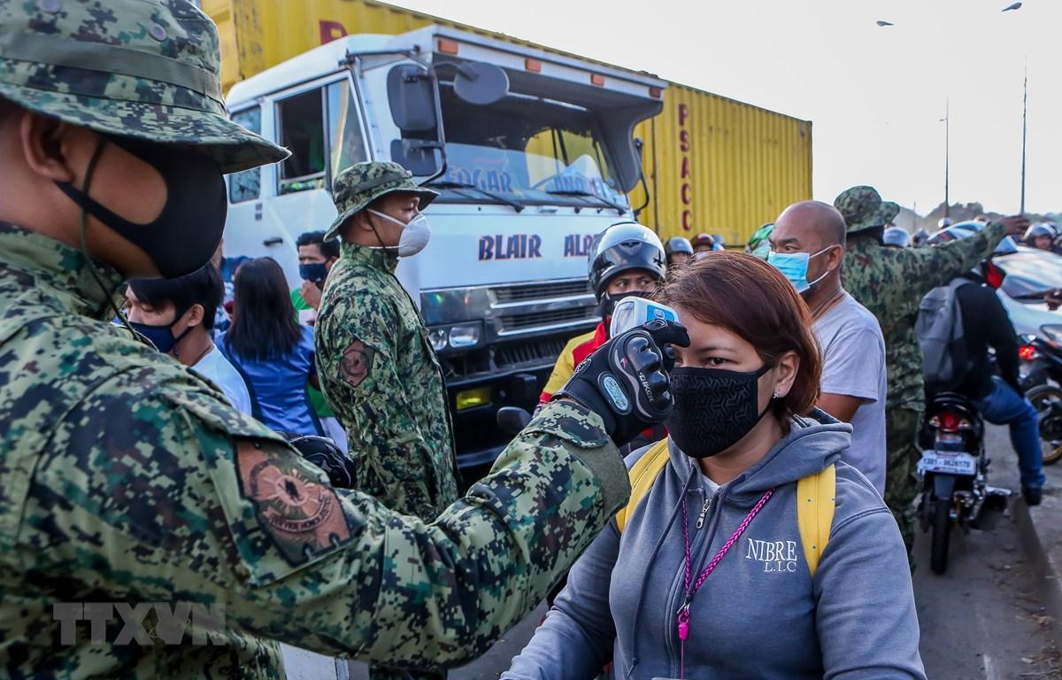 Cảnh sát kiểm tra thân nhiệt nhằm ngăn chặn sự lây lan của dịch COVID-19 tại một trạm kiểm soát ở Quezon, Philippines. (Ảnh: THX/TTXVN)