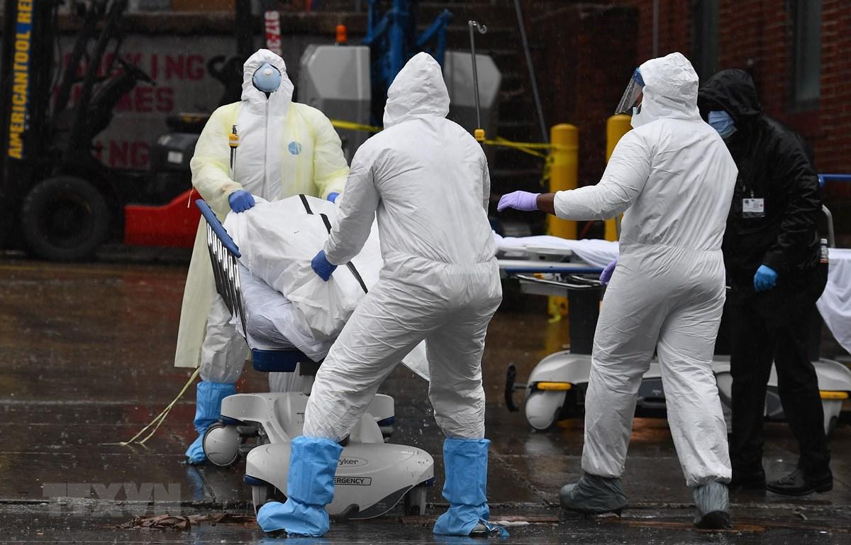 Nhân viên y tế chuyển thi thể bệnh nhân mắc COVID-19 ra nhà xác dã chiến bên ngoài một bệnh viện ở New York, Mỹ. (Ảnh: AFP/TTXVN)