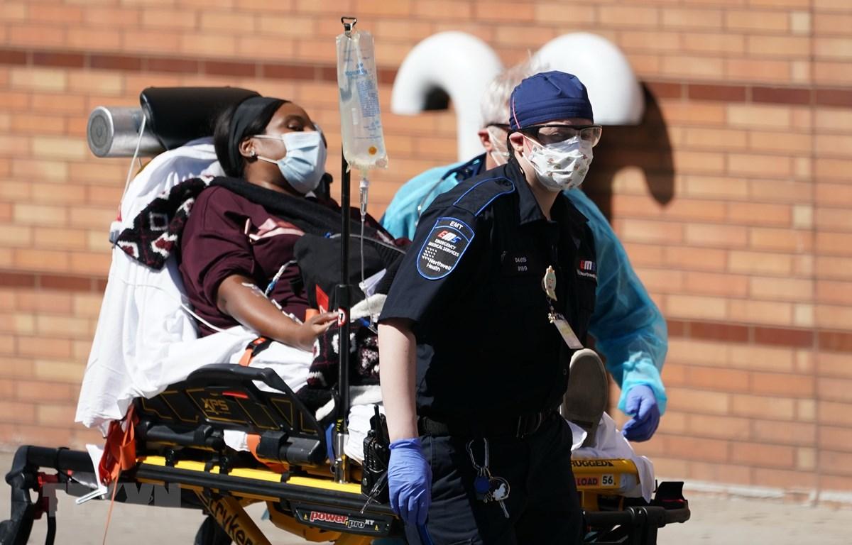 Nhân viên y tế chuyển bệnh nhân mắc COVID-19 tới bệnh viện ở Brooklyn, New York, Mỹ. (Ảnh: AFP/TTXVN)