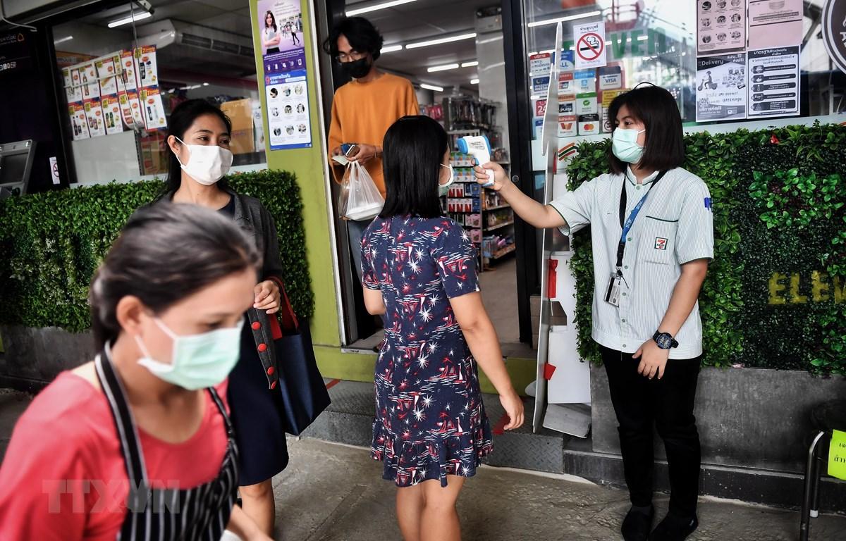 Kiểm tra thân nhiệt cho người dân tại Bangkok, Thái Lan. (Ảnh: AFP/TTXVN)