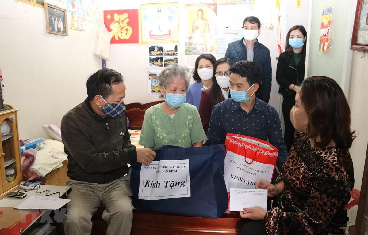 Đại diện lãnh đạo quận Hoàn Kiếm trao quà bà Nguyễn Thị Hằng (76 tuổi), thương binh 4/4 ở 91 Lý Thường Kiệt, phường Cửa Nam, là người già yếu, hết tuổi lao động, sống một mình. (Ảnh: Anh Tuấn – TTXVN)
