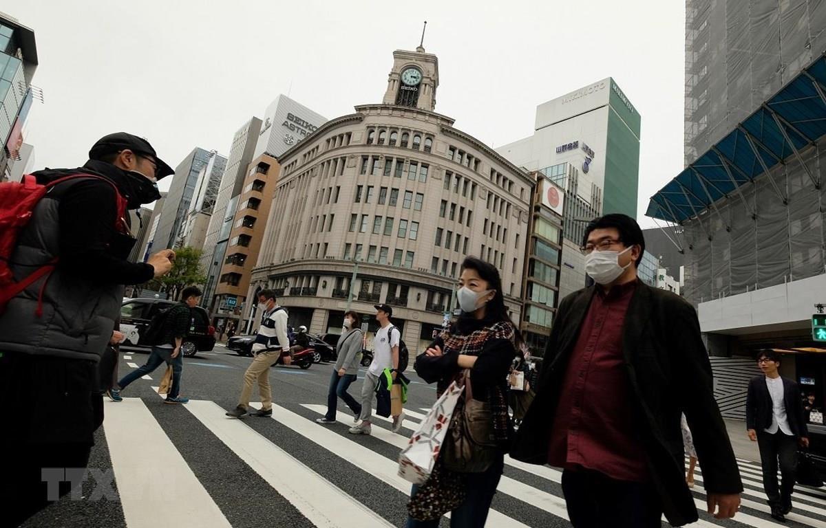 Người dân Nhật Bản đeo khẩu trang phòng tránh lây nhiễm COVID-19. (Ảnh: AFP/TTXVN)