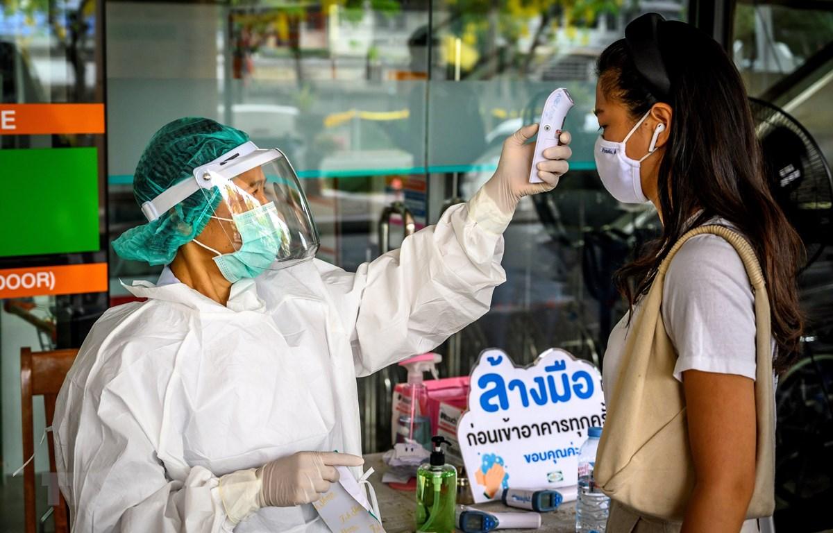 Nhân viên y tế kiểm tra thân nhiệt phòng lây nhiễm COVID-19 tại Bangkok,Thái Lan. (Ảnh: AFP/TTXVN)