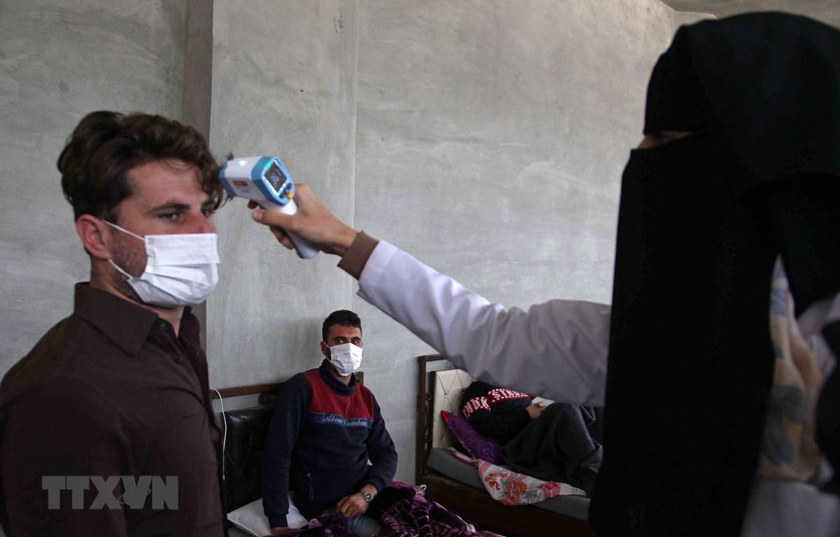 Nhân viên y tế kiểm tra thân nhiệt nhằm ngăn chặn sự lây lan của dịch COVID-19 tại Idlib, Syria. (Ảnh: AFP/TTXVN)