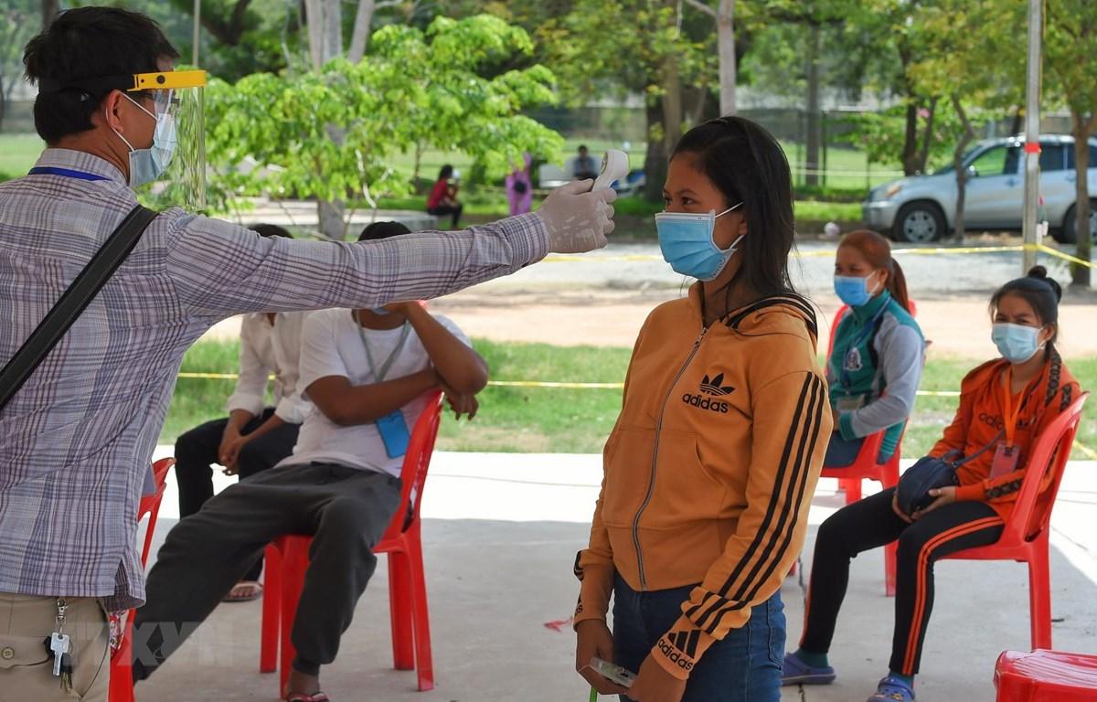 Kiểm tra thân nhiệt các lao động nhập cư nhằm ngăn chặn sự lây lan của dịch COVID-19 tại Phnom Penh, Campuchia. (Ảnh: AFP/TTXVN)
