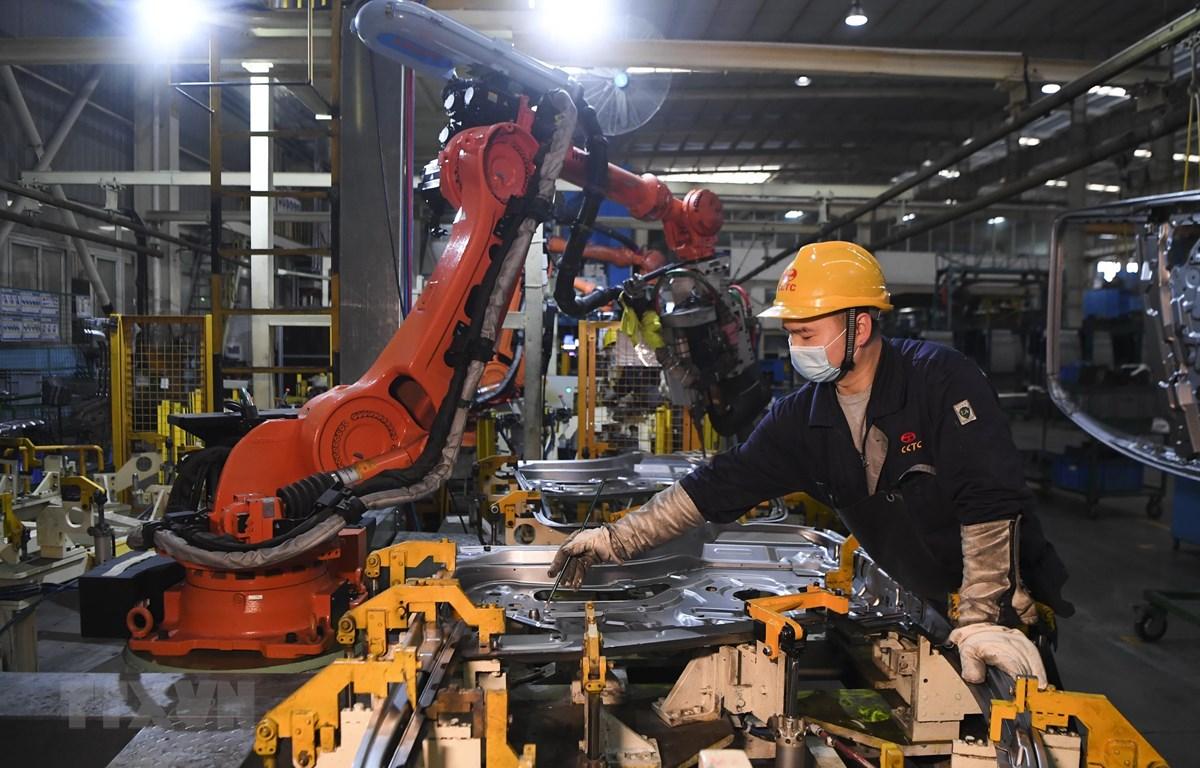 Công nhân làm việc bên trong một nhà máy ở Du Bắc, tỉnh Trùng Khánh, Trung Quốc ngày 11/3. (Ảnh: THX/TTXVN)