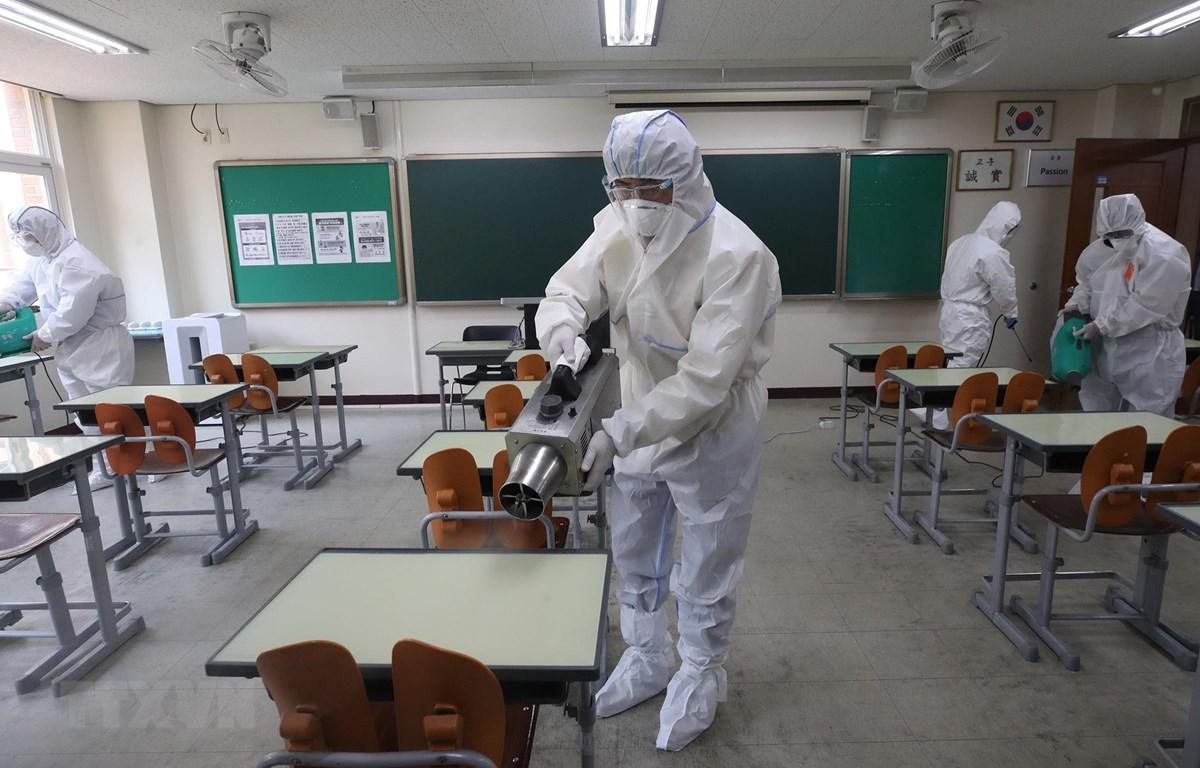 Nhân viên kiểm dịch phun khử trùng một lớp học ở Seoul, Hàn Quốc. (Ảnh: Yonhap/TTXVN)