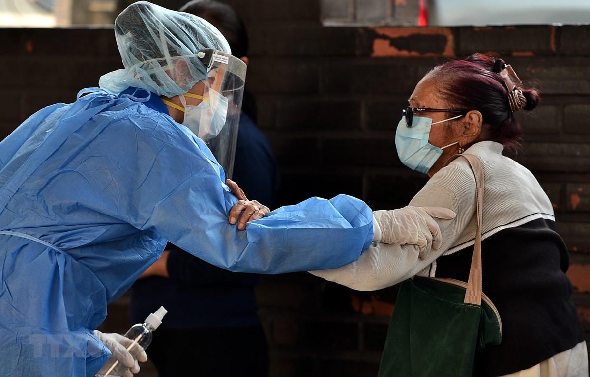 Nhân viên y tế giúp đỡ một bệnh nhân nhiễm COVID-19 tại bệnh viện ở Tegucigalpa, Honduras. (Ảnh: AFP/TTXVN)