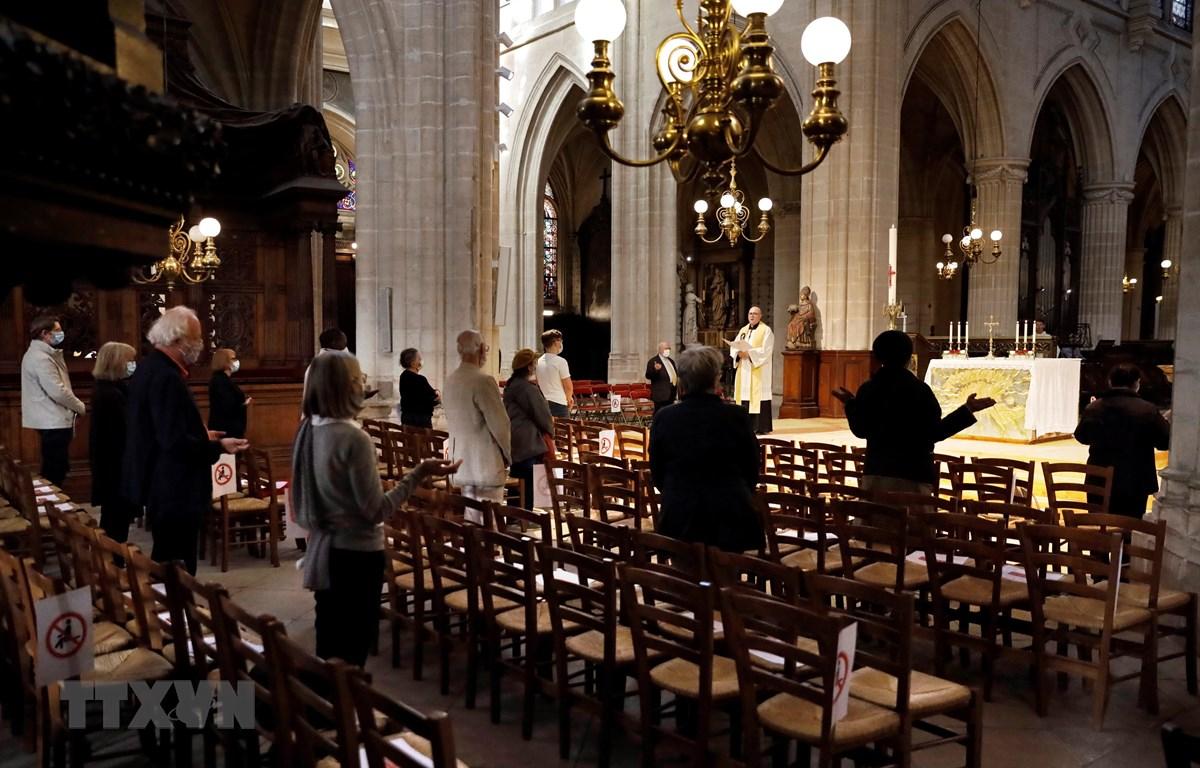 Các tín đồ Thiên chúa giáo cầu nguyện tại một nhà thờ ở Paris, Pháp ngày 24/5. (Ảnh: AFP/TTXVN)