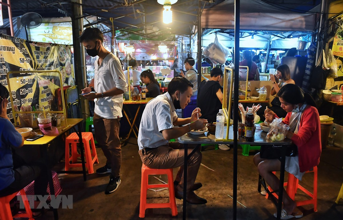 Một quán ăn tại Bangkok, Thái Lan, sử dụng tấm chắn nhựa trên bàn ăn để ngăn chặn sự lây lan của COVID-19. (Ảnh: AFP/TTXVN)