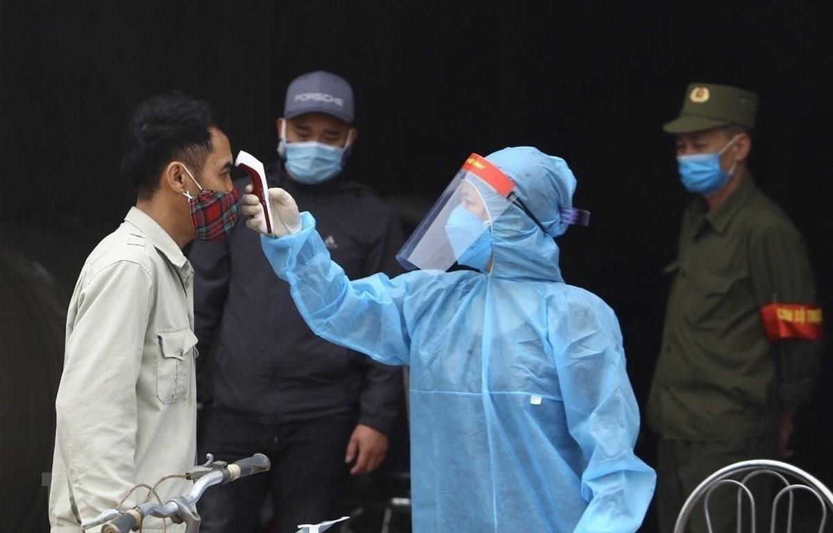 Nhân viên y tế kiểm tra thân nhiệt của người dân. (Ảnh: Minh Quyết/TTXVN)