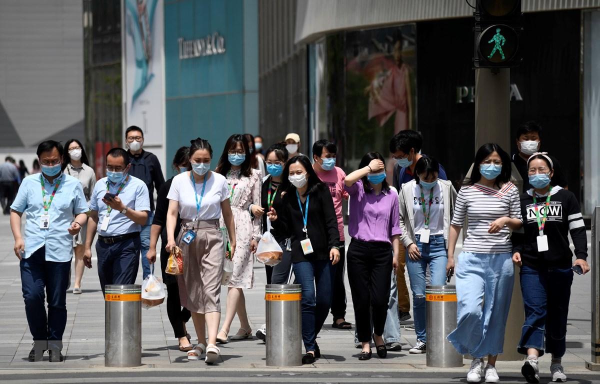 Người dân đeo khẩu trang phòng dịch COVID-19 tại Bắc Kinh, Trung Quốc ngày 20/5. (Ảnh: AFP/TTXVN)