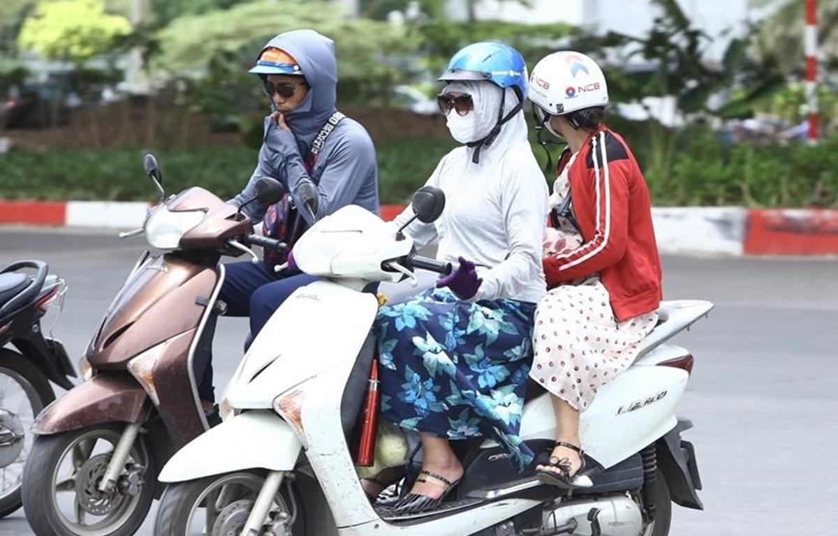Người dân mặc áo chống nắng khi ra đường. (Ảnh: Minh Quyết/TTXVN)