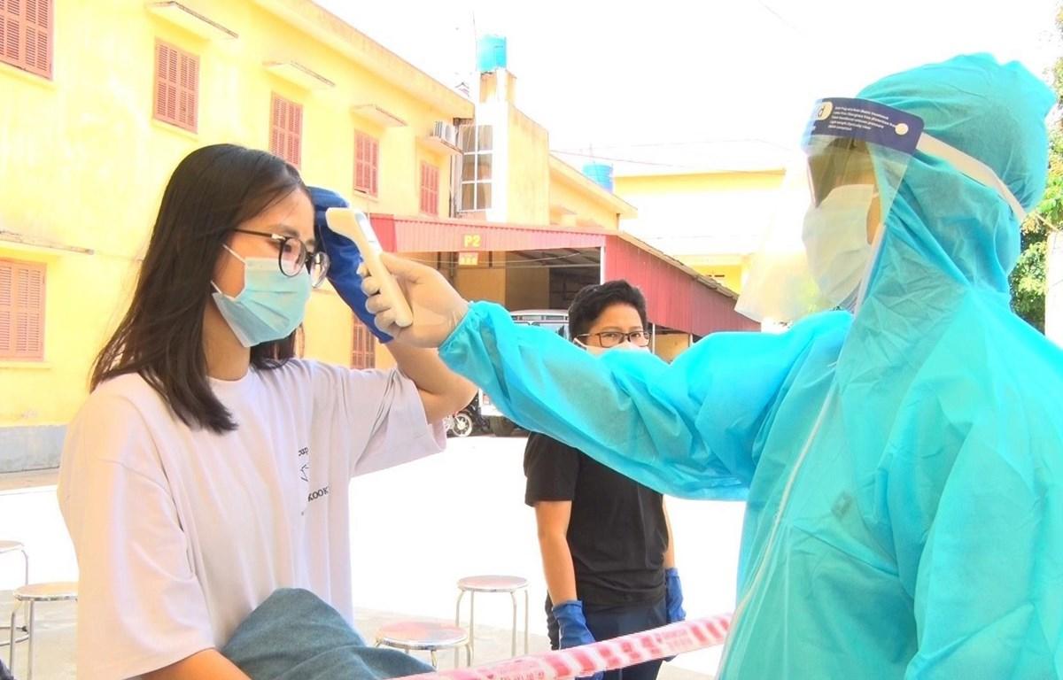 Bác sĩ kiểm tra thân nhiệt cho công dân. (Ảnh: Đinh Tuấn/TTXVN)