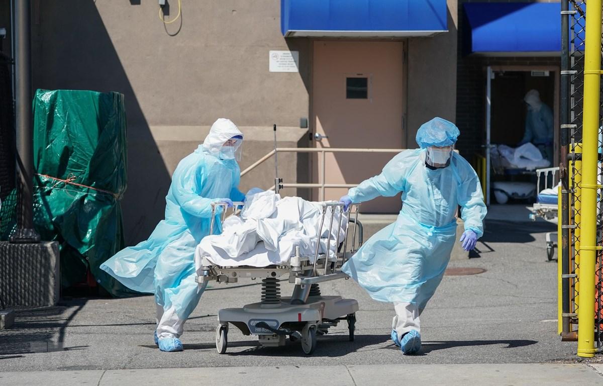 Nhân viên y tế chuyển thi thể bệnh nhân mắc COVID-19. (Ảnh: AFP/TTXVN)