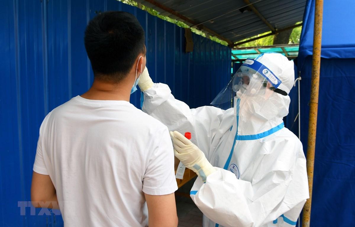 Nhân viên y tế lấy mẫu xét nghiệm COVID-19 cho người dân tại Bắc Kinh, Trung Quốc ngày 20/6. (Ảnh: THX/TTXVN)