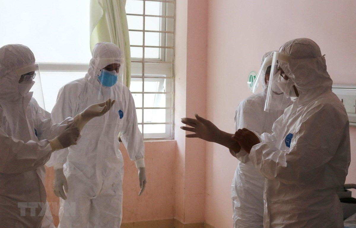 Đội phản ứng nhanh của Bệnh viện Chợ Rẫy hướng dẫn nhân viên y tế Bệnh viện Bà Rịa mặc trang phục bảo hộ. (Ảnh: TTXVN phát)