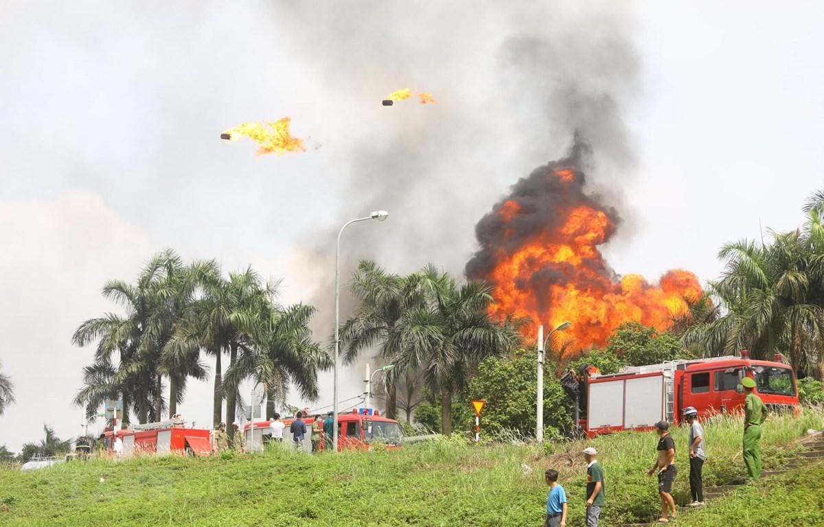 Một số thùng phuy chứa hóa chất phát nổ, bay lên cao hàng chục mét. (Ảnh: Huy Hùng/TTXVN)