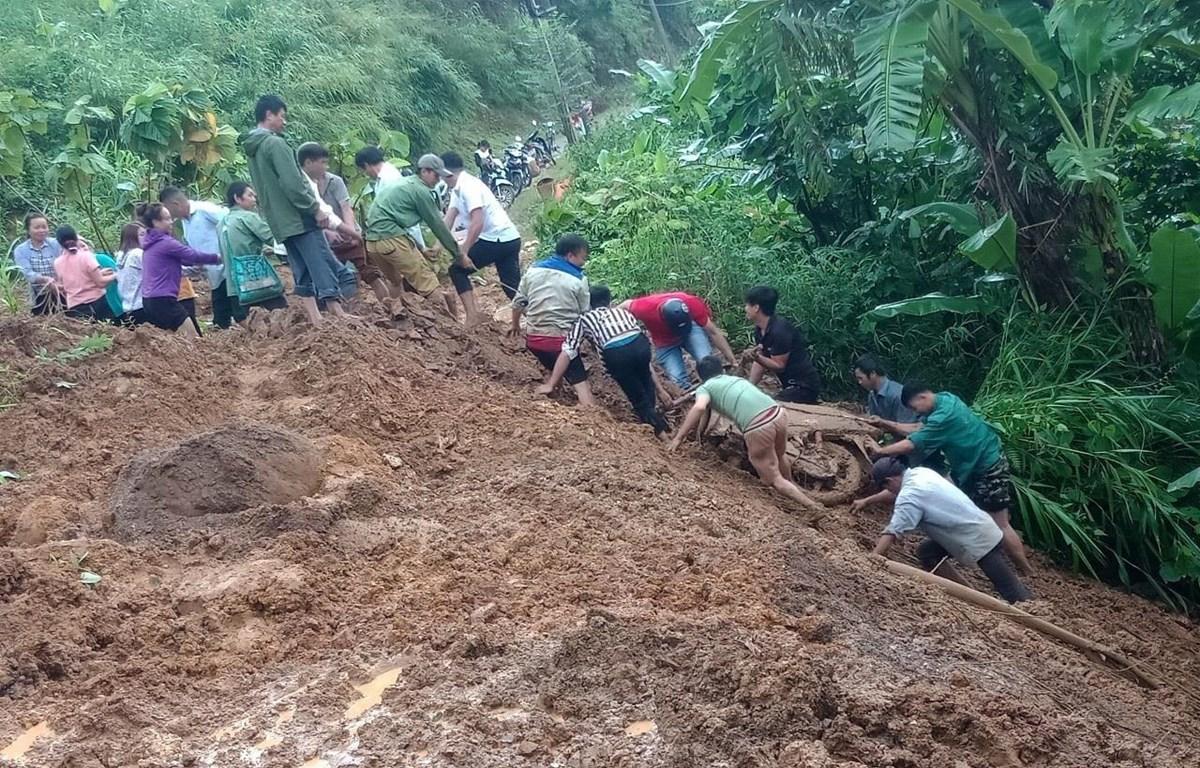 Người dân hỗ trợ đưa xe máy của chị Lò Thị Châu (ở tỉnh Lai Châu) từ dưới vực lên. (Ảnh: TTXVN phát)