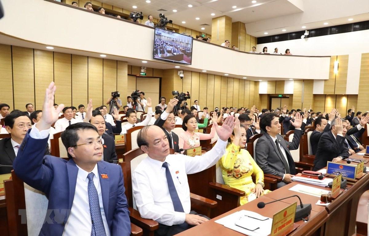 Các đại biểu thông qua chương trình kỳ họp. (Ảnh: Văn Điệp/TTXVN)