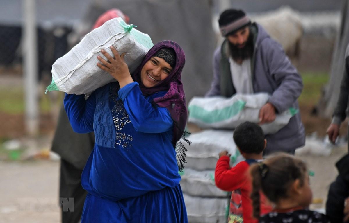 Người tị nạn Syria nhận hàng viện trợ tại trại tị nạn ở thị trấn Mehmediye, Syria, ngày 21/2. (Ảnh: AFP/TTXVN)
