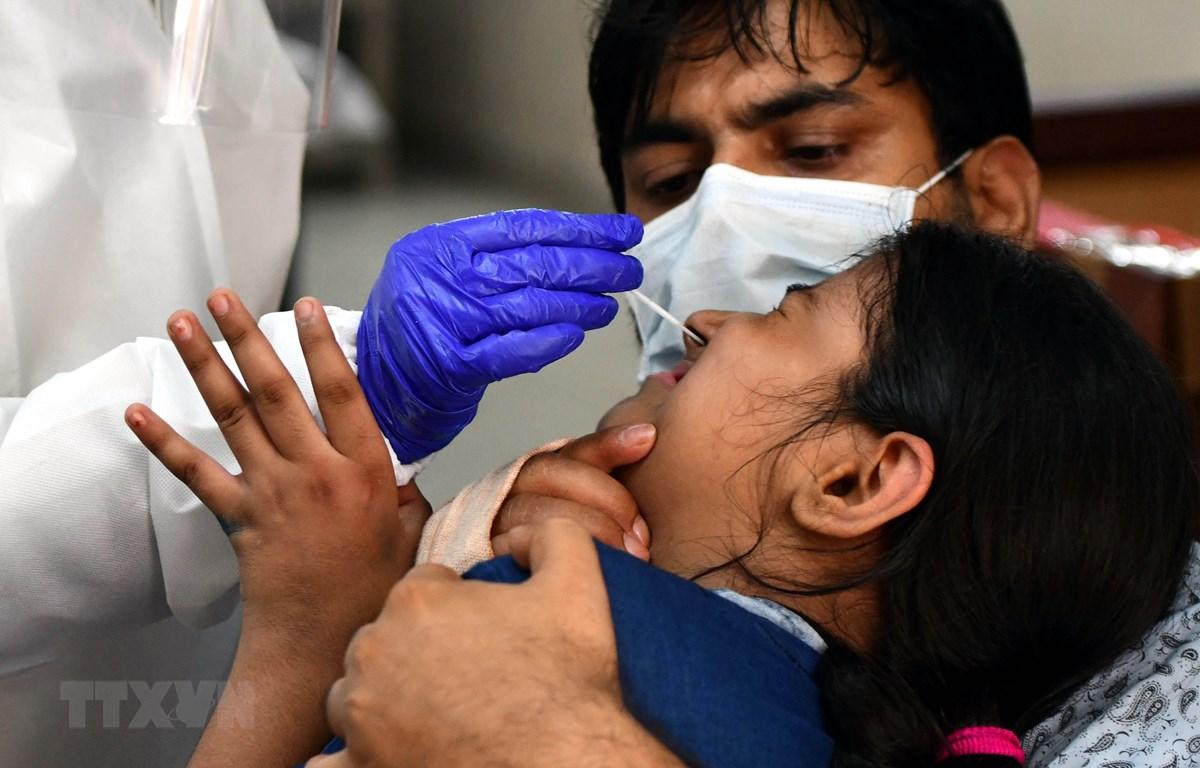 Nhân viên y tế lấy mẫu dịch xét nghiệm COVID-19 cho người dân tại New Delhi, Ấn Độ. (Ảnh: THX/TTXVN)
