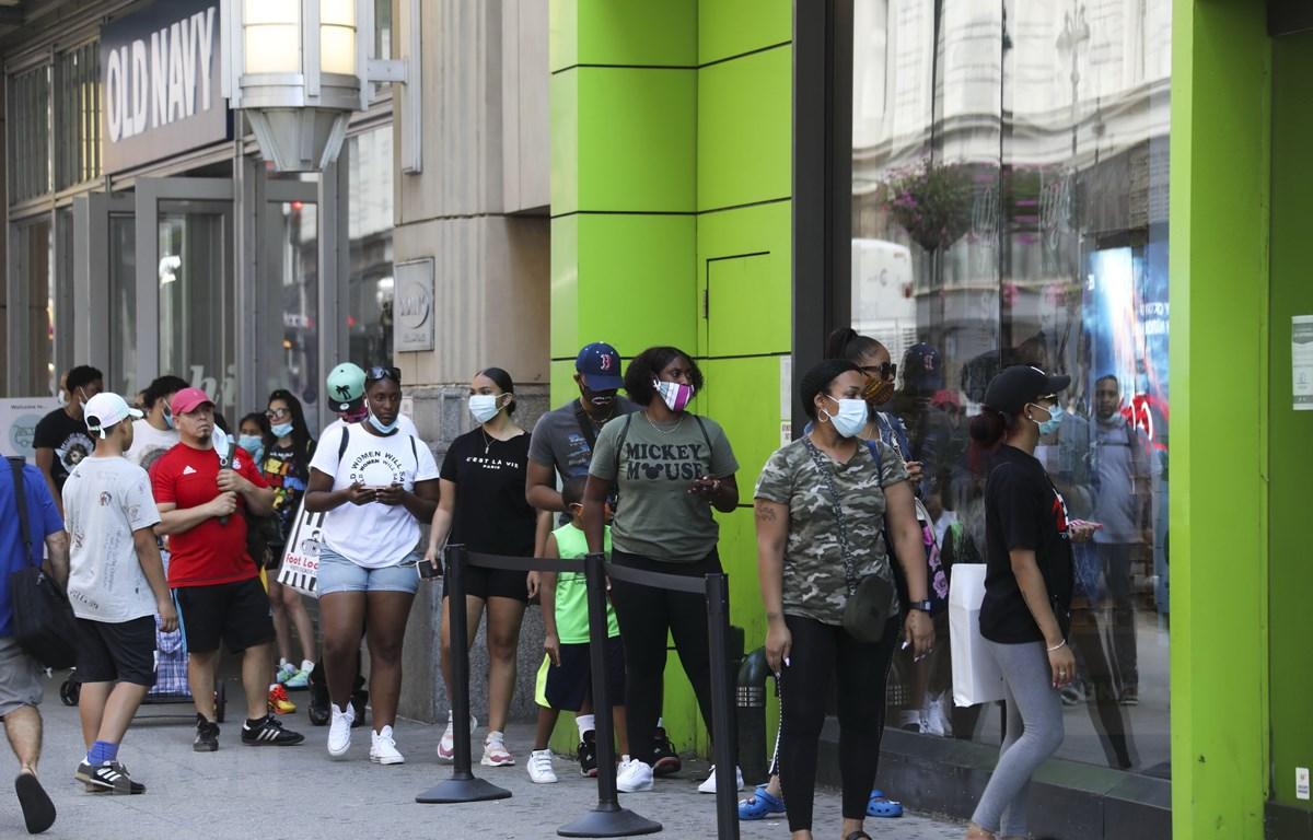 Người dân đeo khẩu trang phòng lây nhiễm COVID-19 khi xếp hàng bên ngoài một cửa hàng ở New York, Mỹ. (Ảnh: THX/TTXVN)