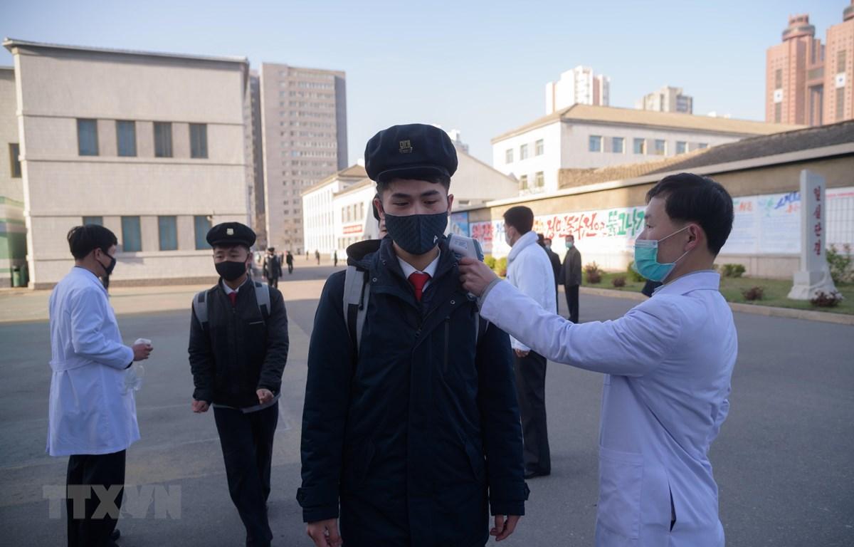 Kiểm tra thân nhiệt phòng lây nhiễm COVID-19 tại trường đại học Y ở Bình Nhưỡng, Triều Tiên. (Ảnh: AFP/TTXVN)
