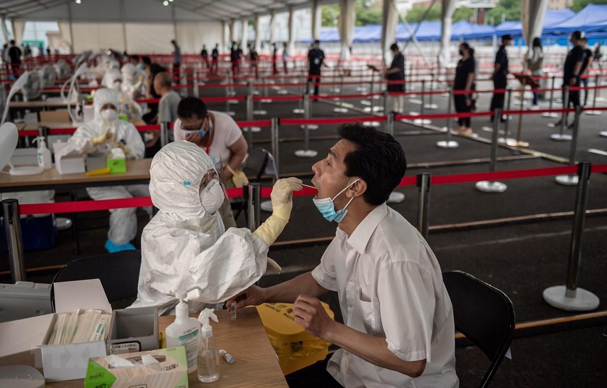 Nhân viên y tế lấy mẫu dịch xét nghiệm COVID-19 cho người dân tại Bắc Kinh, Trung Quốc, ngày 24/6/2020. (Ảnh: AFP/TTXVN)