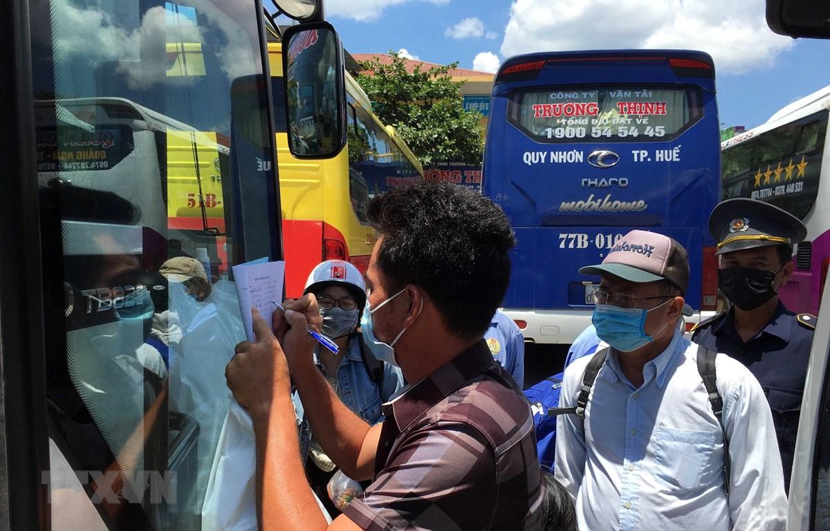 Hành khách đi trên những phương tiện giao thông khai báo thông tin cá nhân tại Bến xe phía Nam tỉnh Thừa Thiên-Huế. (Ảnh: Đỗ Trưởng/TTXVN)