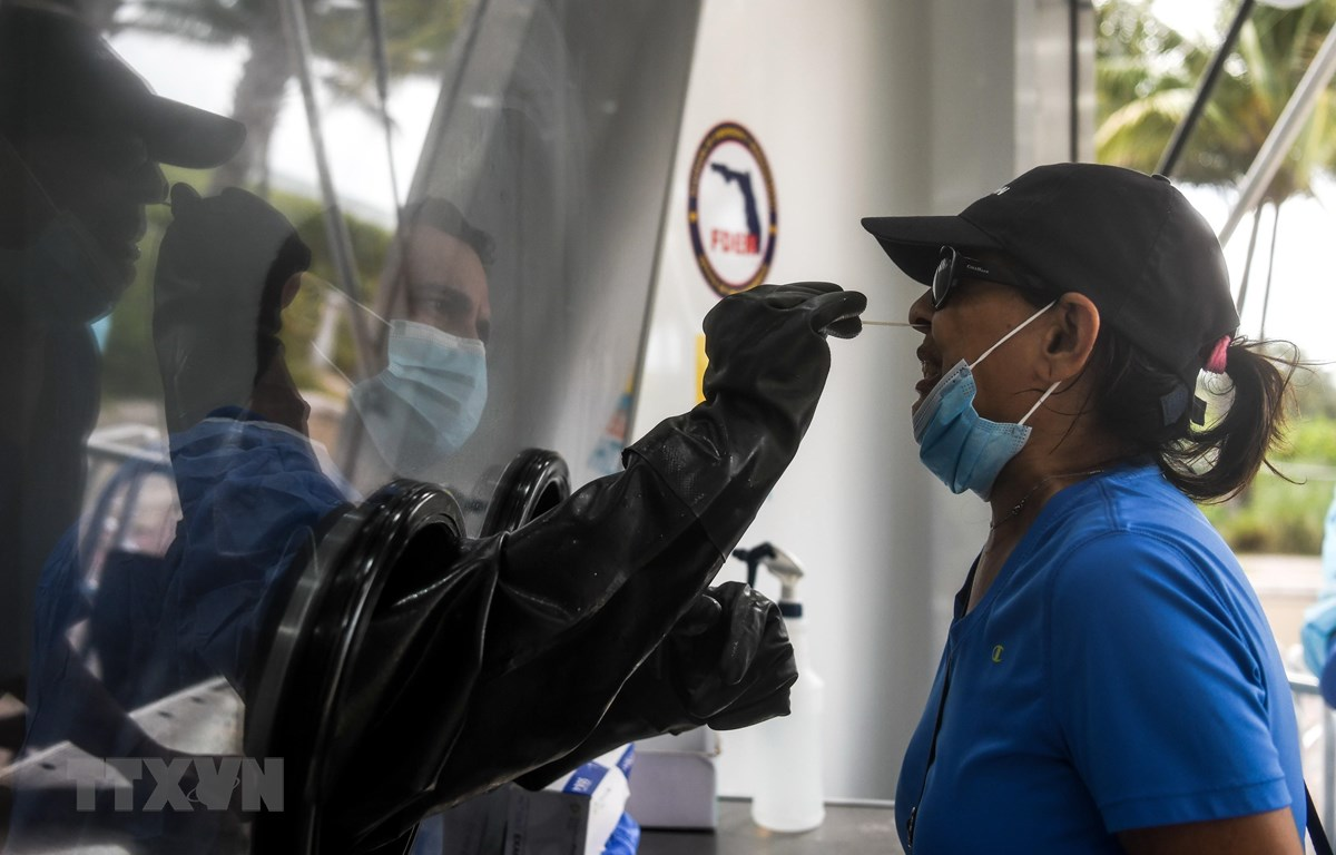 Nhân viên y tế lấy mẫu dịch xét nghiệm COVID-19 cho người dân tại Miami Beach, bang Florida, Mỹ. (Ảnh: AFP/TTXVN)