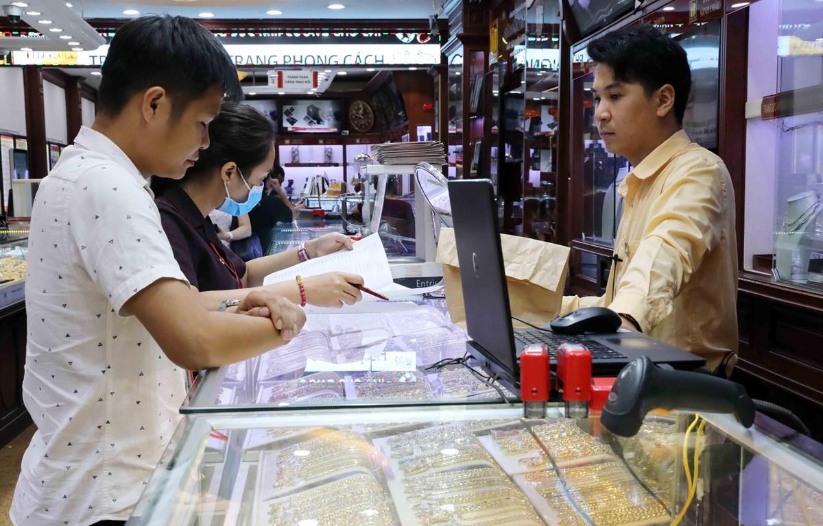 Khách mua bán vàng tại Công ty Kinh doanh vàng bạc Bảo Tín Minh Châu. (Ảnh: Trần Việt - TTXVN)