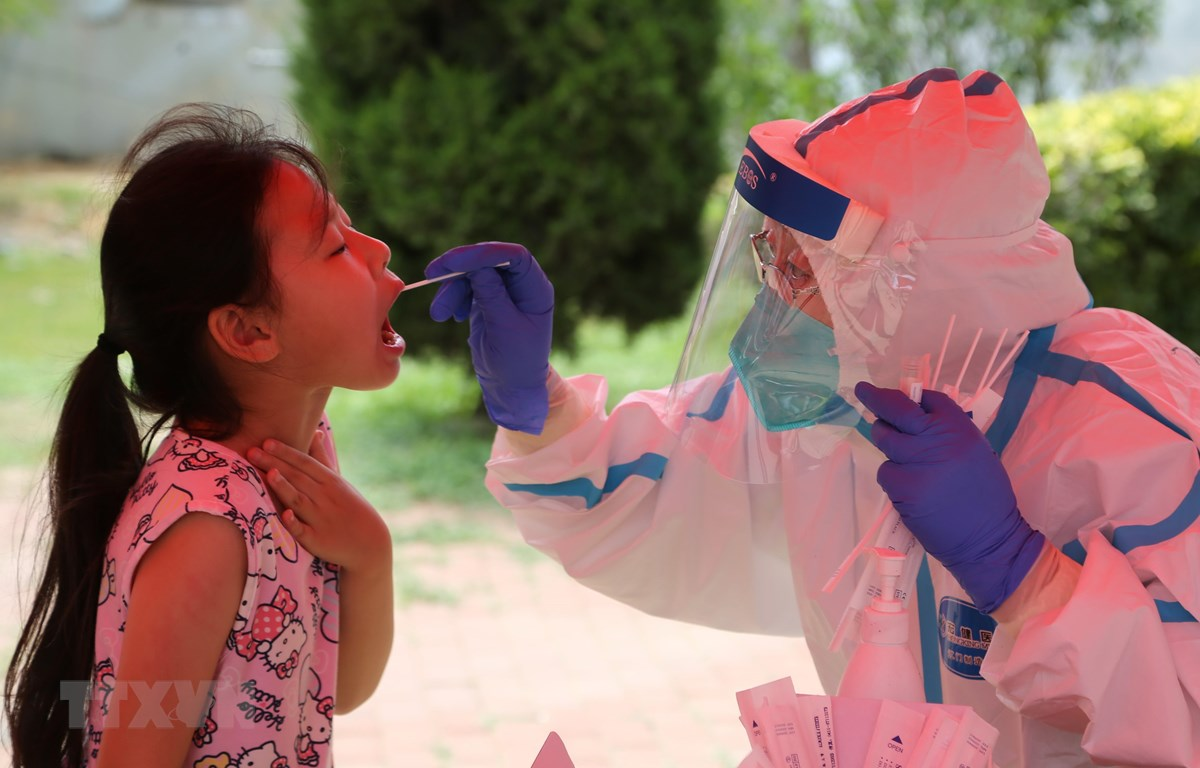 Nhân viên y tế lấy mẫu xét nghiệm COVID-19 tại Đại Liên, tỉnh Liêu Ninh, Trung Quốc. (Ảnh: AFP/TTXVN)