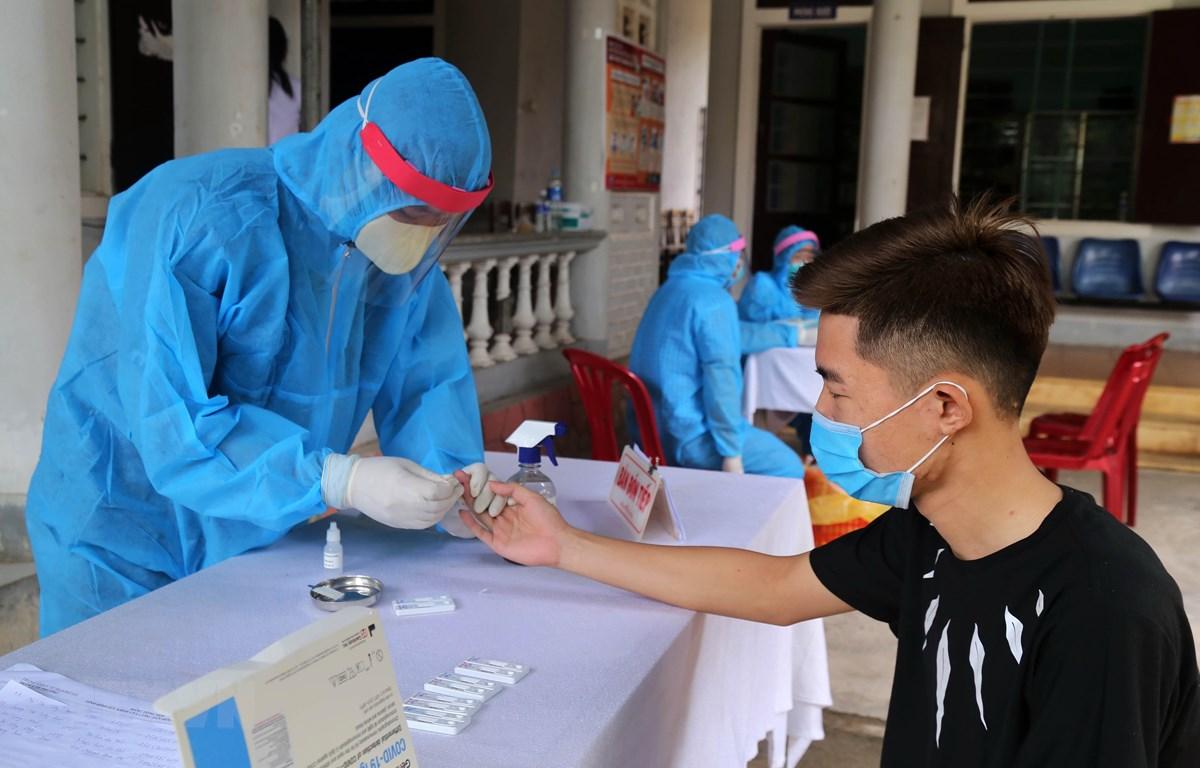 Các cán bộ y tế tiến hành xét nghiệm nhanh COVID-19 cho người dân trở về từ vùng có dịch. (Ảnh: Hồ Cầu/TTXVN)