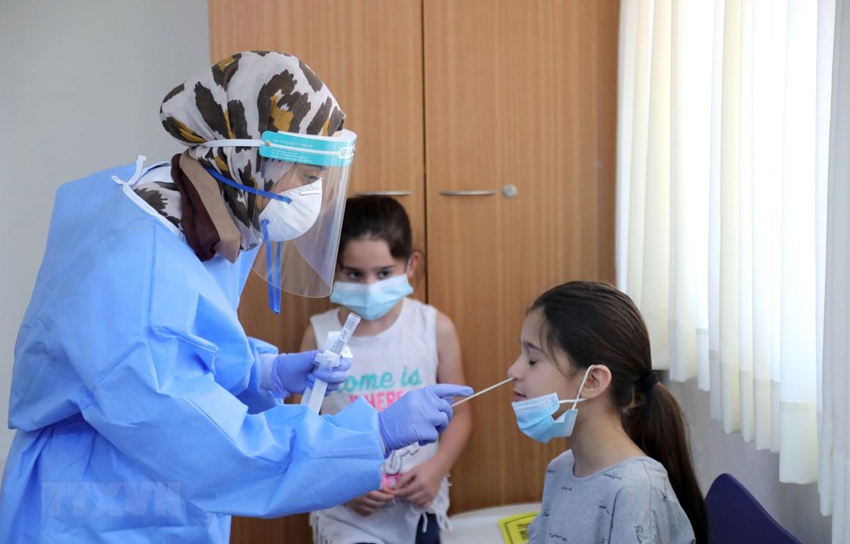 Nhân viên y tế lấy mẫu dịch xét nghiệm COVID-19 cho trẻ em tại thành phố Or Yehuda, Israel. (Ảnh: THX/TTXVN)