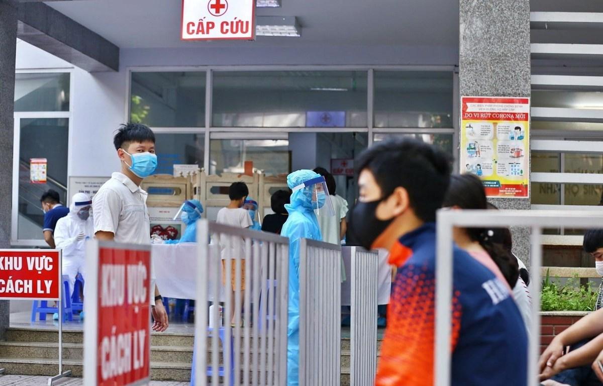 Người dân đến lấy mẫu xét nghiệm được bố trí ngồi chờ theo khu vực quy định. (Ảnh: Minh Quyết/TTXVN)