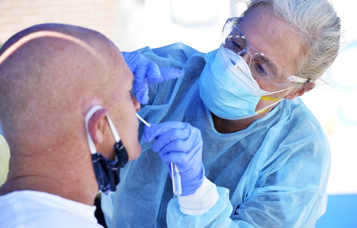 Nhân viên y tế lấy mẫu xét nghiệm COVID-19 tại Revere, Massachusetts, Mỹ. (Ảnh: AFP/TTXVN)