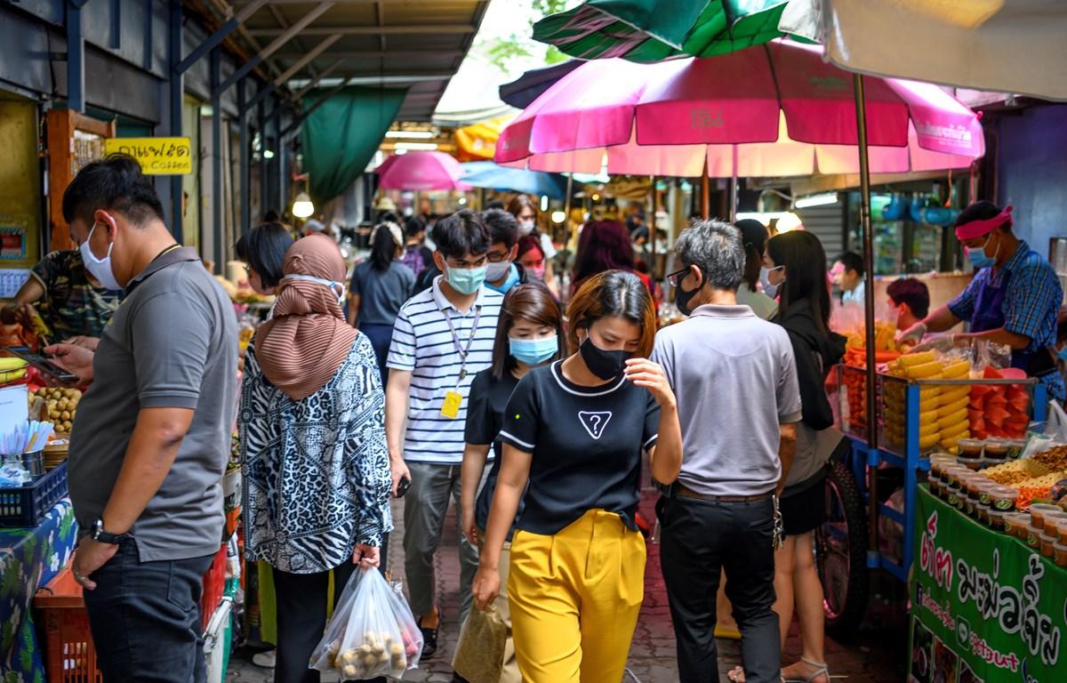 Người dân đeo khẩu trang phòng lây nhiễm COVID-19 khi mua sắm tại một khu chợ ở Bangkok, Thái Lan. (Ảnh: AFP/TTXVN)