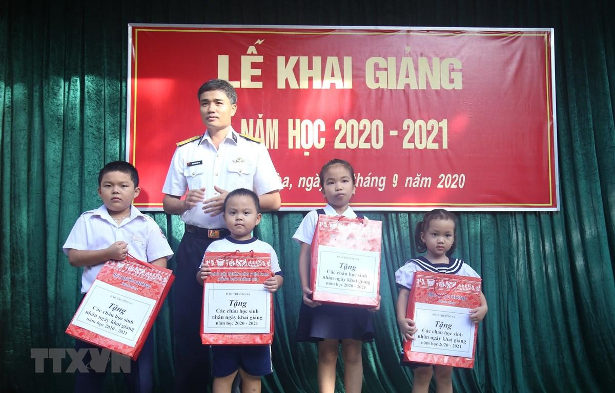 Đại diện chính quyền địa phương thị trấn Trường Sa tặng quà động viên cho các học sinh Trường Tiểu học thị trấn Trường Sa, nhân dịp khai giảng năm học mới. (Ảnh: TTXVN phát)